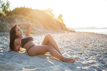 Sensual young woman in bikini laying on the sand at the beach during sunset.