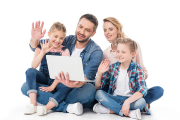happy family using laptop while sitting on floor isolated on white