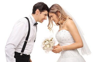 Furious newlywed couple pushing their heads against each other