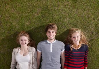 Three friends lying smiling
