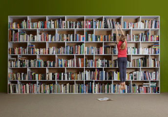 Girl jumping for book on high shelf