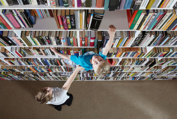 Girl helping boy climb bookshelves