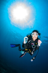 Beautiful Scuba diver smile with underwater Ambient light in the blue sea.