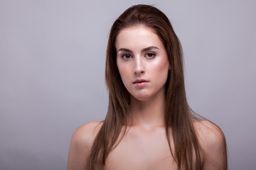 Gorgeous model in bra with natural make up on gray background in studio photo. Beauty and fashion.