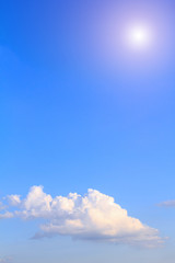 Blue sky background with white clouds, rain clouds and sunshine on sunny summer or spring day.
