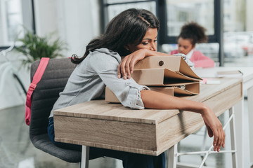 portrait of tired businesswoman lying on folders at workplace with daughter behind