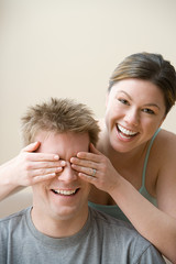 Woman covering husband's eyes