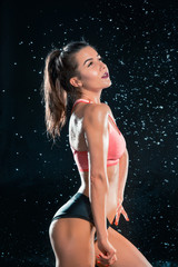 Young tanned fit woman with beautiful sporty buttocks and slim with water drops