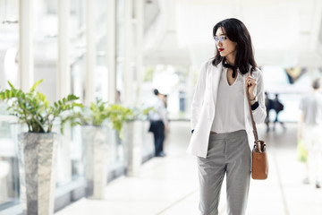 Pretty elegant  serious Asian businesswoman standing at shopping mall.