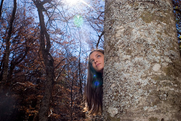 Young woman hiding behind a tree