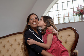 Daughter kissing mother on sofa
