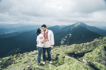 man and woman kissing each other on the top of the mountain