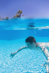 Teenage boy, swimming underwater at spa resort swimming pool. Divided view from underwater.