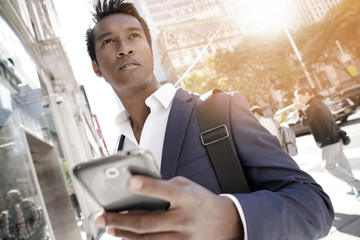 Businessman using smartphone in Manhattan city centre