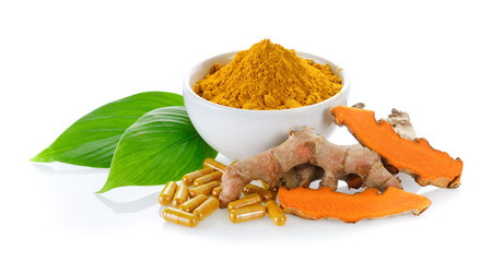 fresh turmeric and turmeric capsules on white background