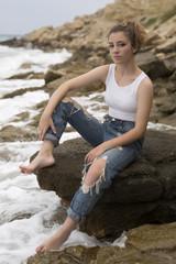 Teenage girl sitting on the rocks.