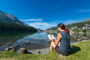 Young woman reads a book in front of a mountain lake