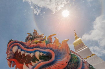 Abstract soft blurred and soft focus sun halo with symbol Nagas, sanctuary, temple, sky cloud by the beam, light and lens flare effect tone.The public properties at Wat Phra That Choeng Chum,Thailand.