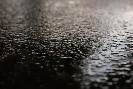 Wet asphalt sidewalk background after heavy rain soft focus.
