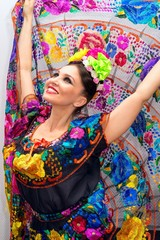 beautiful smiling mexican woman in traditional mexican dress hands up holding the skirt as a background like peacock