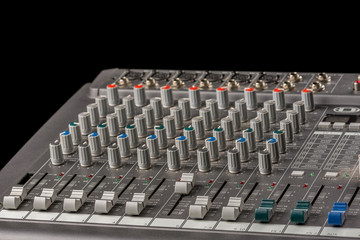 Audio mixing console with knobs and sliders and black background