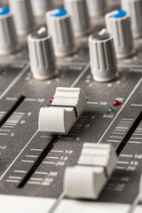 Closeup macro audio mixing console knobs and sliders.