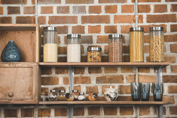 Close-up view of various cereals and spices in glass containers on wooden shelves