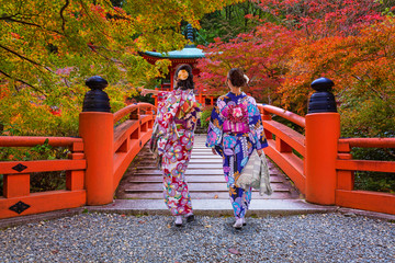 Photo sur Toile Japon Women in kimonos walking at the colorful maple trees in autumn, Kyoto. Japan