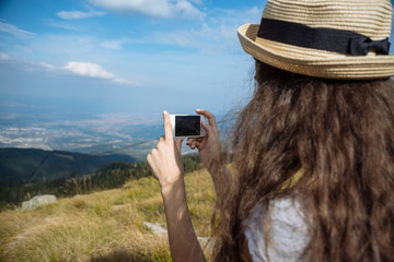 Girl with smartphone on the slope of the mountain of Vitosha and the blue sky. View of the city of Sofia