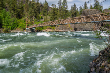 Wooden bridge across the river on a background of the green forest. Dark blue rough river. Scenic landscape. Riverside state park, Bowl and Pitcher, Spokane area, Eastern Washington, USA.