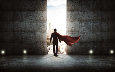 Businessman in a suit and cape stand on stair against concrete wall with huge door ,sunrise scene city skyline outdoor view . Wall mural