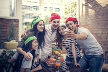 Young people with friends have a mini party holding smartphone for selfie together , people with party concept, vintage tone.