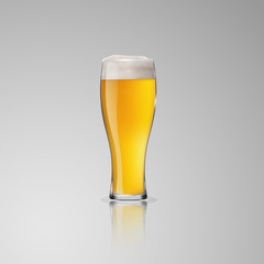 A clear glass with a light beer.