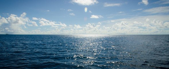 A panoramic scene of blue sky and the ocean with sunbeam shine above