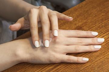 Feminine hands apply the cream on the skin.