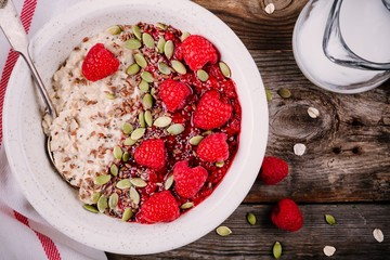 Healthy breakfast: oatmeal with fresh raspberries, flax seeds and pumpkin seeds