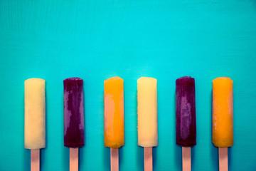 青い背景にあるポップでカラフルなフルーツアイスキャンデー