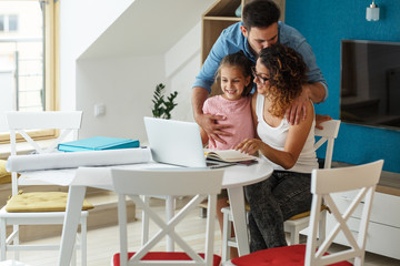 Happy family in living room. Mother calculate home budget and savings,while her husband and daughter support her with group hug.