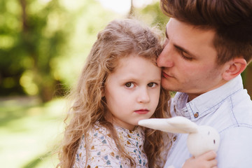 Father hugging his daughter. Little girl holding her rabbit toy and looking straight into camera. Family spent weekend in the park, having fun. Happy childhood. Parent's love.