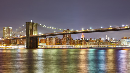 Panoramic photo of the Brooklyn Bridge with city lights reflected in East River at Night, New York City, USA.