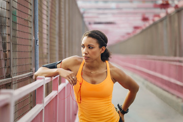 A woman resting after a workout on a bridge in New York City.