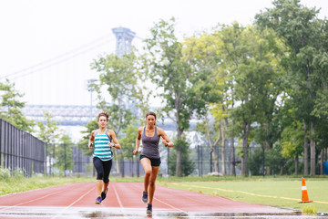 Two women sprinting on a track with an urban bridge behind them.