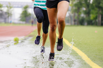 Close-up of two women's legs running through a puddle on an athletic field.
