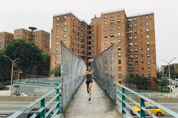A woman sprinting over a bridge on her workout.