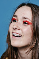 Teenager with a brace, smiling away from camera, with red eye make up and brunette hair.