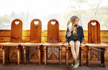 Girl sitting on wooden chairs in log cabin.
