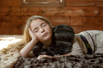 Girl laying in bed in log cabin.