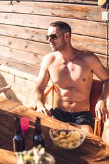 Guy in briefs sitting under sunshine
