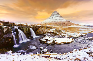 View of the Kirkjufell Mountain with Kirkjufellsfoss Waterfall at dusk in Iceland.