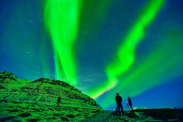 View of the northern light with photographers expecting near Kirkjufell Mountain in Iceland.